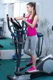 Fitness Woman. Happy woman training at the gym on cross trainer Stock Images
