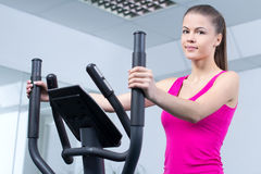 Fitness Woman. Happy woman training at the gym on cross trainer Royalty Free Stock Photo