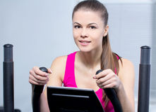 Fitness Woman. Happy woman training at the gym on cross trainer Royalty Free Stock Images