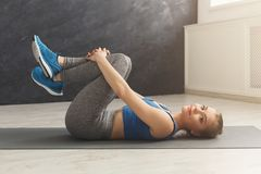 Fitness woman have rest after training. Fitness woman have rest, lying on mat and hugging her knees after training at gym. Bodybuilding, healthy lifestyle Royalty Free Stock Photos