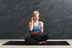 Fitness woman having rest in gym. Happy fitness woman having rest and listening to music. Young girl sitting on mat in headphones. Bodybuilding, healthy Royalty Free Stock Images