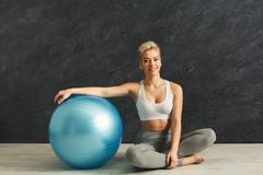 Fitness woman having rest near fitness ball indoors. Happy fitness woman having rest near fitness ball at gym. Young slim girl relaxing after making aerobics Stock Photos