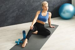 Fitness woman having rest indoors. Fitness woman having rest, sitting on mat in gym. Young slim girl relaxing after making aerobics exercise. Healthy lifestyle Royalty Free Stock Photos