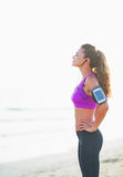 Fitness woman in headphones relaxing after running on beach Royalty Free Stock Images