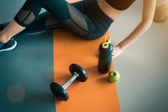 Fitness woman with Healthy workout equipment on gym floor. Exercise and Body build up concept. Beauty and sport theme. Relax and stock photo