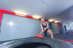 Fitness woman hitting wheel tire with hammer sledge in the gym. royalty free stock images