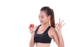 Fitness woman holding apple and showing ok sign. Royalty Free Stock Photos