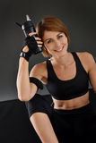 Fitness woman holding a bottle sitting on the floor Stock Photos