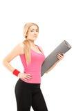Fitness woman holding an exercising mat and posing Stock Photos