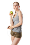 Fitness woman holding a green apple and listening music. Isolated on white Royalty Free Stock Image