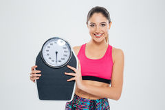 Fitness woman holding weighing machine Royalty Free Stock Photos