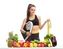 Fitness woman holding a weight scale and a measuring tape behind Royalty Free Stock Images