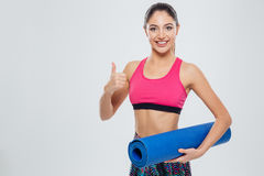 Fitness woman holding yoga mat and showing thumb up Royalty Free Stock Image
