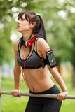 Fitness woman on the horizontal bar outdoors in park Stock Images