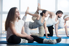 Fitness woman injured. Injured unhappy women sitting in sports club, touching her leg muscles, suffering from pain after working out in class with group of stock images
