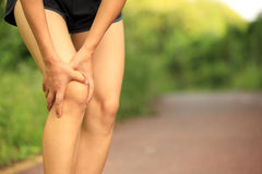 Fitness woman jogger hold her sports injured leg at forest trail Royalty Free Stock Photography