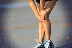 Fitness woman jogger hold her sports injured leg at forest trail Royalty Free Stock Images
