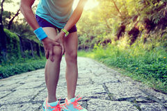 Fitness woman jogger hold her sports injured leg at forest trail Stock Photo