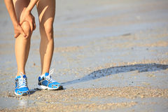 Fitness woman jogger hold her sports injured leg at seaside Stock Photo