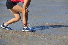 Fitness woman jogger hold her sports injured leg at seaside Stock Images