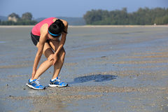 Fitness woman jogger hold her sports injured leg at seaside Royalty Free Stock Photography