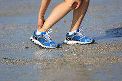 Fitness woman jogger hold her sports injured leg at seaside Royalty Free Stock Images