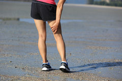 Fitness woman jogger hold her sports injured leg at seaside Stock Photography