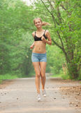 Fitness woman jogging. Young beautiful fitness woman jogging in park Stock Photography