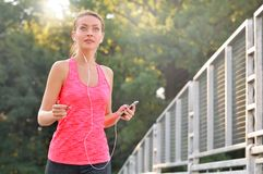 Fitness woman jogging. Fitness woman running. Woman jogging on urban road and listen music. Fitness girl training outdoor Stock Photos