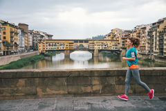 Fitness woman jogging in front of ponte vecchio in florence, ita Stock Images