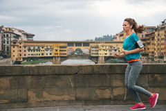Fitness woman jogging in front of ponte vecchio. In florence, italy Stock Photo