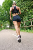 Fitness woman jogging outdoors. Fitness young woman jogging outdoors Stock Photography
