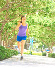 Fitness Woman Jogging In Park. Full length of young fitness woman jogging at park in morning. Vertical shot Stock Photography