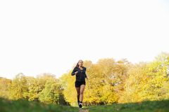 Fitness woman jogging in park. Image of fitness woman running in autumn park outdoors. Female athlete jogging in park. Caucasian female fitness model Royalty Free Stock Photos