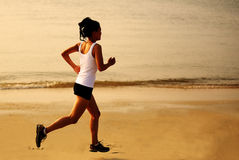 Fitness woman jogging at sunrise/sunset beach Stock Images