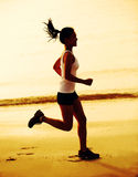 Fitness woman jogging at sunrise/sunset beach Stock Image