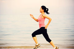 Fitness woman jogging at sunrise/sunset beach Royalty Free Stock Photos