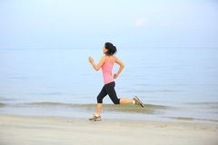Fitness woman jogging at sunrise/sunset beach Royalty Free Stock Photography