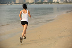 Fitness woman jogging at sunrise/sunset beach Royalty Free Stock Photo