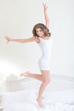 Fitness woman jumping. On the bed Stock Image