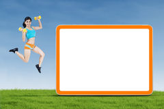 Fitness woman jumping with empty board Stock Photo
