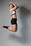 Fitness woman jumping of joy. On a gray background Stock Image