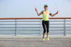 Fitness woman jumping rope at seaside royalty free stock photo