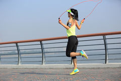 Fitness woman jumping rope at seaside stock photo