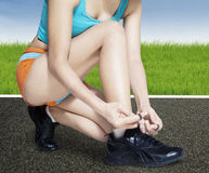 Fitness woman lacing her shoes Royalty Free Stock Images