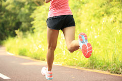 Fitness woman legs running at forest trail Stock Photo