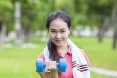 Fitness woman lifting dumbbell weight training outside. In the garden Royalty Free Stock Images