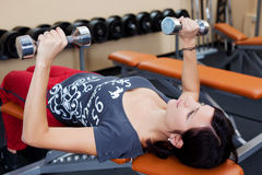 Fitness woman. Lifting dumbbells and lying in a close up shot Stock Photo