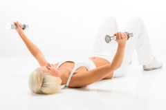 Fitness woman lifting dumbbells lying white floor Stock Images