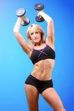 Fitness woman. Lifting weights above her head isolated on blue background. Caucasian female fitness model Stock Image